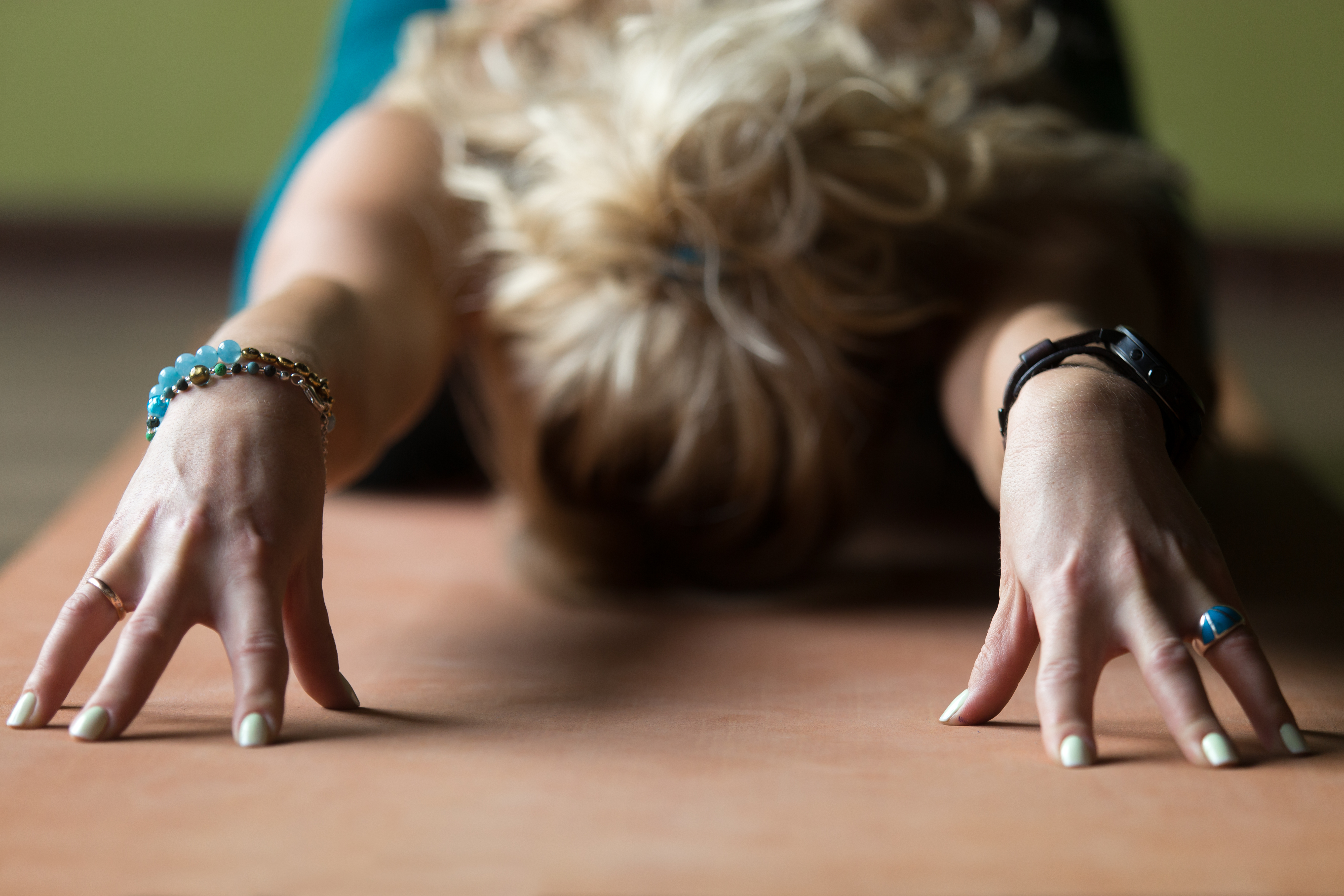 Sporty beautiful blond young woman in sportswear working out indoors, doing Balasana on fingertips, Child Posture on orange eco mat, resting, relaxing, close-up of fingers